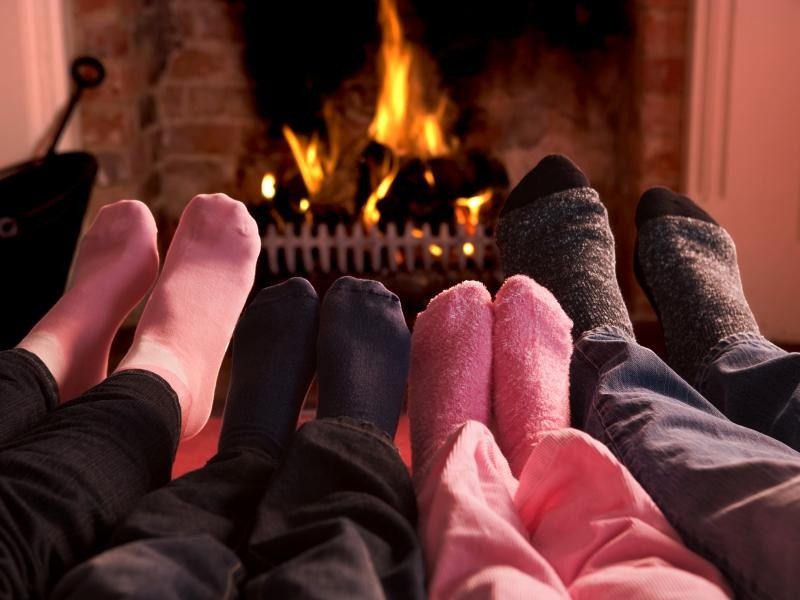 Family warming feet at a fireplace